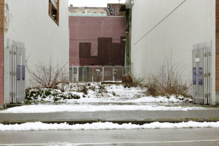 A wide shot of the x̱aw̓s shew̓áy̓ New Growth《新生林》garden seen from the street, with its gates open and a light covering of snow spread over its grounds.